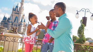 A dad and 2 daughters eat Mickey-shaped ice cream bars with Cinderella Castle in the background