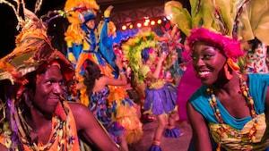 Artistas vestidos de forma vibrante no evento noturno Discovery Island Carnivale do Disney's Animal Kingdom Park