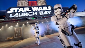 Two Imperial Stormtroopers with blasters at the ready stand guard in front of the lit marquee of Star Wars Launch Bay