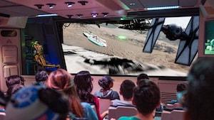 Um público sentado assiste às imagens em uma tela mostrando uma perseguição aérea na qual um TIE fighter persegue e dispara contra a Millennium Falcon