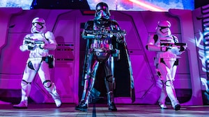 Captain Phasma holds her blaster rifle with an armed stormtrooper to either side