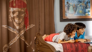 Two young boys read a story together while lying on their stomachs on a boat shaped bed within a pirate themed room at Disney's Caribbean Beach Resort