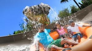 Un père, son fils et sa fille descendent une glissade d'eau et passent sous une chute d'eau à bord d'un radeau