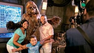 A mother, father and young son smiling while they pose alongside Chewbacca at 'Star Wars' Launch Bay