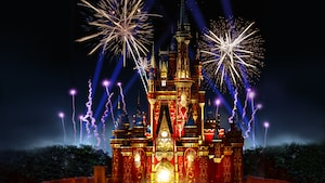 Vibrant colors wash over Cinderella Castle as fireworks light up the sky above