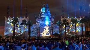 Des visiteurs regardent le Star Wars Galactic Spectacular en face du Grauman's Chinese Theatre qui projette des effets de pointe de Dark Vador, de Princesse Leia et de Luke Skywalker à l'extérieur