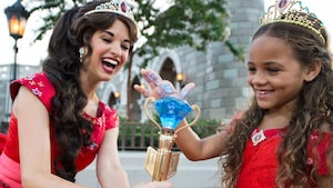 Princess Elena laughs as a girl dressed in a Princess Elena costume touches her crystal scepter