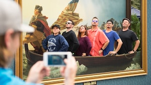 A group of people pose in a front of the painting of Washington Crossing the Delaware while another person snaps a photo