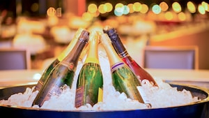 Bottles of champagne arranged in a circular design within a large bowl of ice