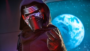 Kylo Ren, wearing a mask, robe and hood, stands inside a spaceship that is closing in on a planet