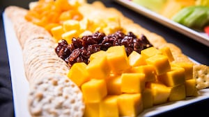 A long platter of fruits, cheeses and crackers