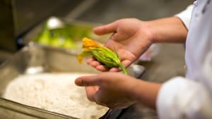 The hand of a chef holding an edible flower directly above a baking dish on a cooking counter
