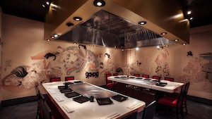 Culturally influenced murals decorate the walls by a duo of hibachi grill tables inside Teppan Edo
