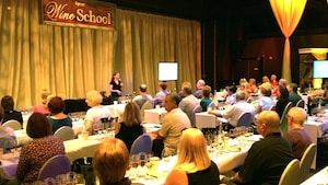 A female host speaking to an excited crowd of Guests in attendance during a Boot Camp Series event