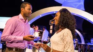 Una pareja bebe vino y se toma de la mano en Party for the Senses en Epcot, en Walt Disney World Resort