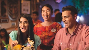 A server smiles while standing behind a young couple gazing in amazement at a dish with sparklers