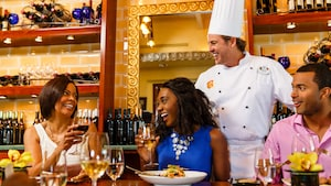 A chef stands behind 3 Guests enjoying wine with their meal