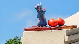 A statue of Remy the rat stands on top of a building next to 2 large sculptures of tomatoes