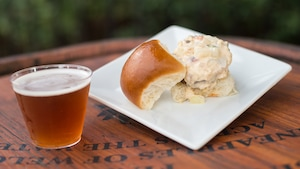 A small glass of beer sits next to a biscuit and gravy dish