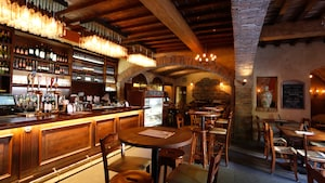The interior of a multi seat wine bar resembles a wine cellar with exposed brick and a wood beam ceiling