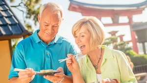 A mature couple excitedly samples from small plates using chopsticks at the Japan Pavilion in Epcot