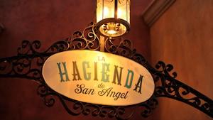 A lantern illuminates an exterior sign for La Hacienda de San Angel in the evening at Epcot