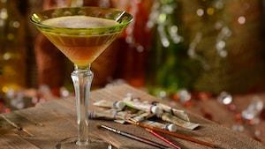 Uma taça elegante de martíni com o coquetel Night Monkey em uma mesa ao lado de tubos de tinta e pincéis de aquarela