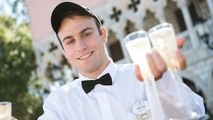 A smiling Epcot Cast Member passing out glasses of champagne around a sunny, outdoor area