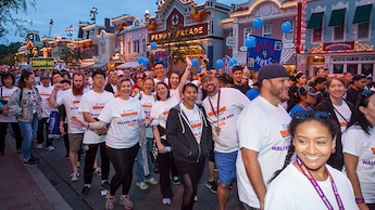 CHOC Walk Pass Holder team members wear their team shirts, hold balloons and stroll through Disneyland Resort