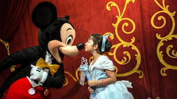 Una joven Huésped vestida como una princesa Disney encantada besa a Mickey Mouse en la nariz