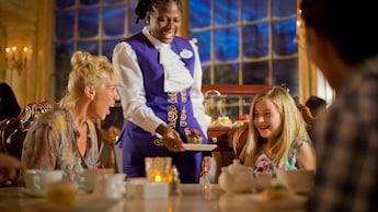 Un miembro del elenco sirve el postre a una niña y su madre en Be Our Guest Restaurant