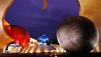 Grandes planetas de colores se iluminan por la noche en la entrada de la misión: SPACE