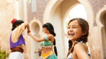 Una niña con el cabello recogido en dos colitas sonríe mientras Aladdin y Jasmine juegan