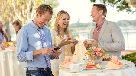 Smiling people in an outdoor setting standing around a high table featuring plates of food, mugs with saucers and a floral centerpiece