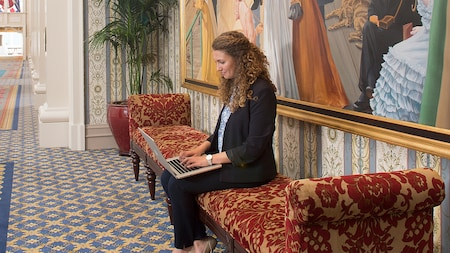A woman typing on a laptop sitting on a cushioned lobby bench