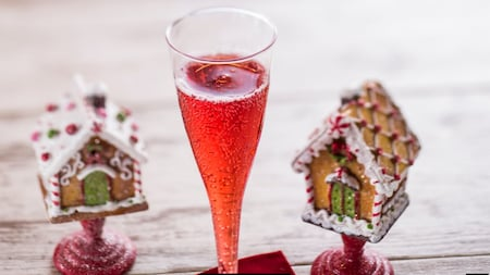 A glass of sparkling wine next to 2 model gingerbread houses