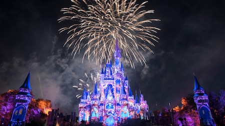 Fireworks erupt in the sky behind Cinderella Castle