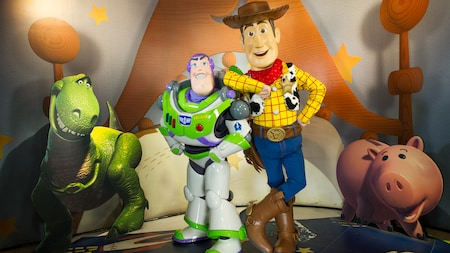 Woody, Buzz Lightyear, Rex and Hamm stand next to each other