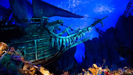 An underwater pirate ship surrounded by treasure, wrecked ships and coral