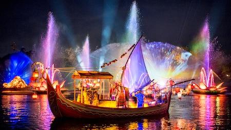 Un barco con lámparas y un actor sobre un río enmarcado con luces, flores de loto gigantes y una fuente de agua