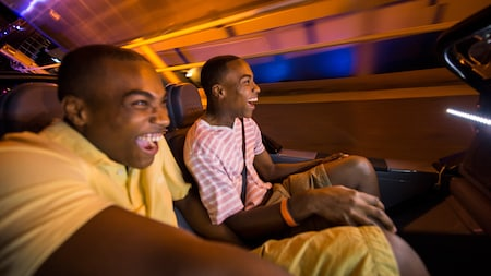 2 men smile as they sit on a roller coaster