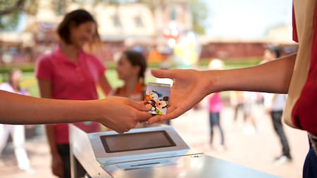 A customer hands over a Disney Gift Card to a Cast Member at a kiosk register