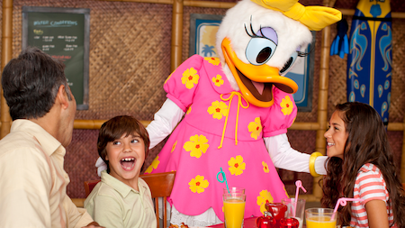 Daisy Duck greets two kids sitting with their dad at breakfast