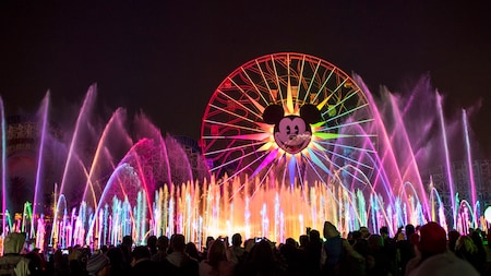 Water effects in front of an illuminated Mickey's Fun Wheel during World of Color