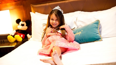 A young girl wearing a tiara and princess dress lies on a bed surrounded by pillows and her Mickey doll