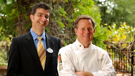 The manager and chef of Napa Rose restaurant stand outside together with lush foliage in the background