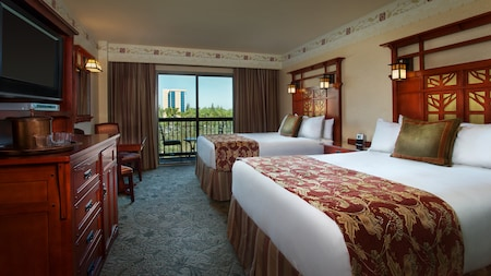 A hotel room features 2 queen beds with high wood headboards, a nightstand and seating on the balcony