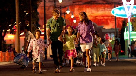 A mom, dad, daughter and son walk hand in hand through Cars Land with other Guests in the background
