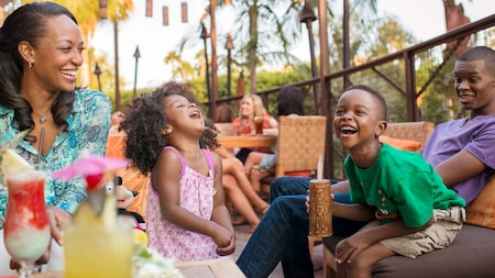 A mom, her 2 sons and young daughter laugh while sitting at an outdoor table with drinks