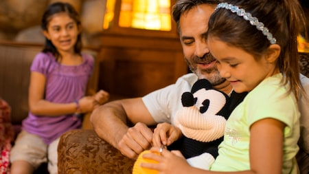 A little girl sits in her dads lap while holding a knitted Mickey Mouse doll as her sister looks on